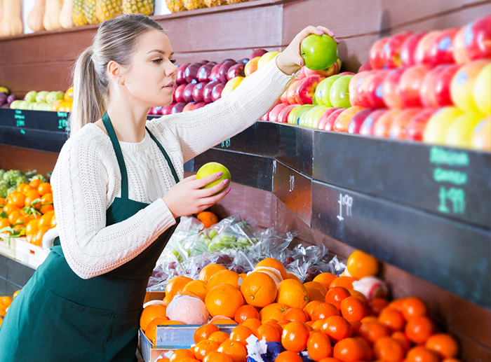 female produce manager stocking fruit on shelf