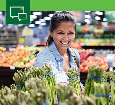 smiling woman selecting asparagus in grocery store